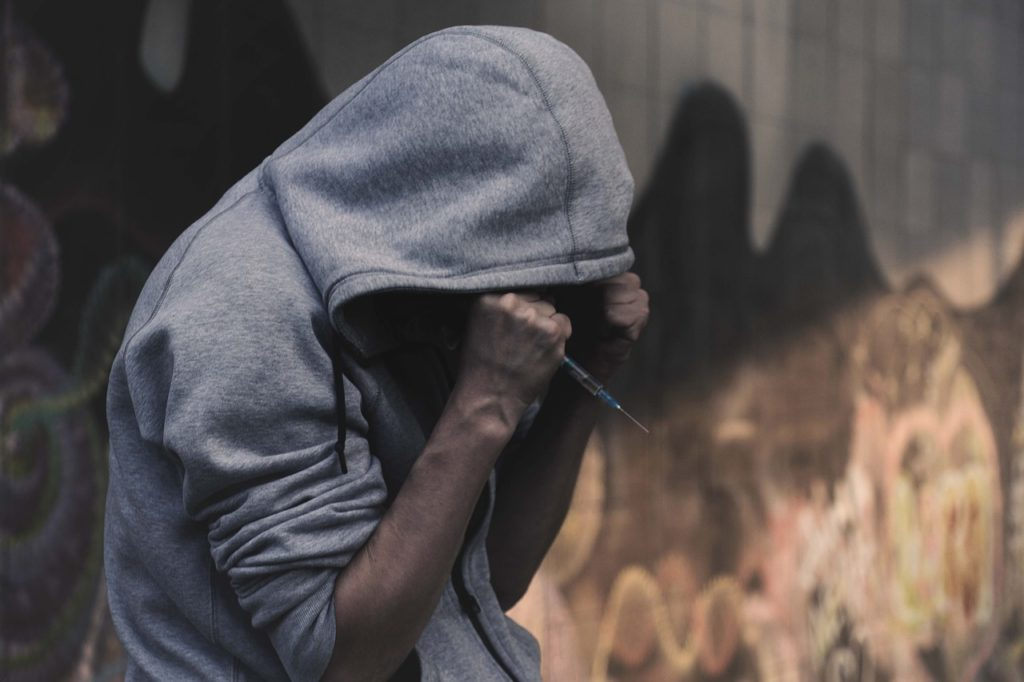 Drug addict wearing a hoodie while holding a syringe.