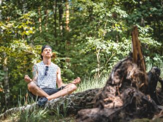 Man meditating outdoors in nature.