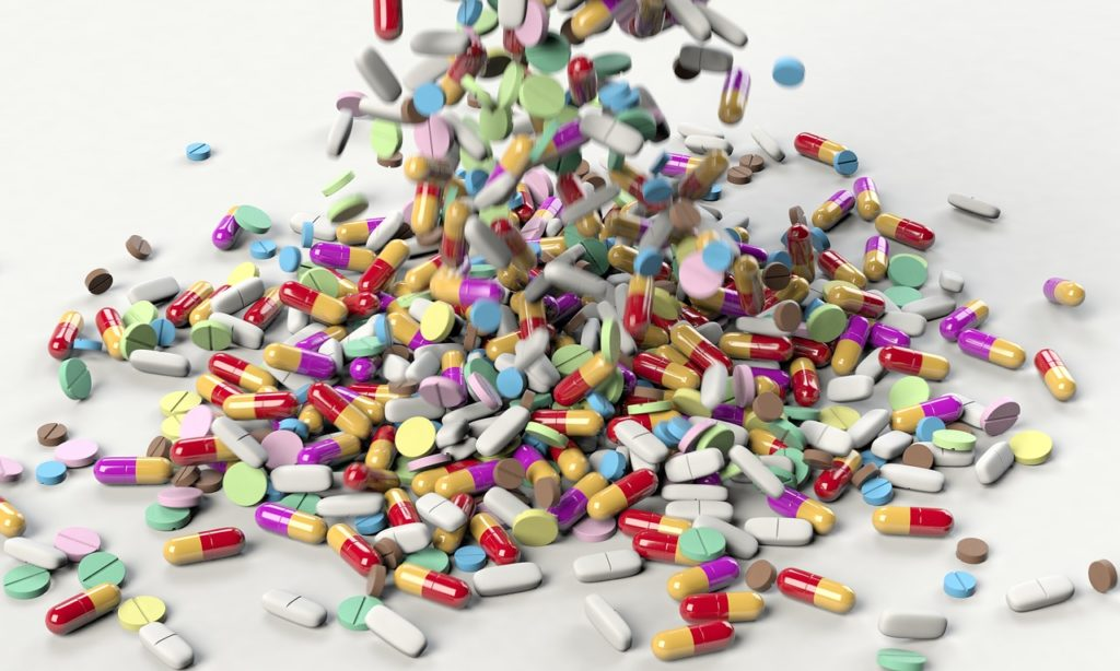 A massive amount of pills and tablet medication being poured onto a white surface.