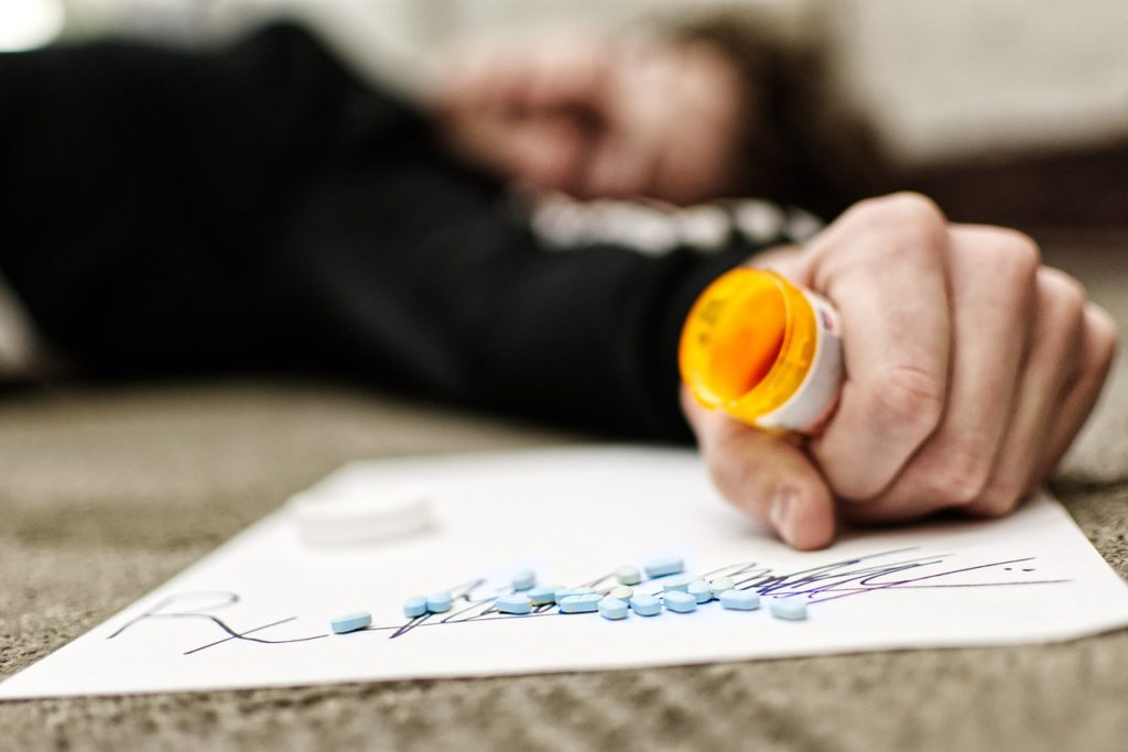 Woman laying on the floor holding an opened pill bottle with pills on the floor.