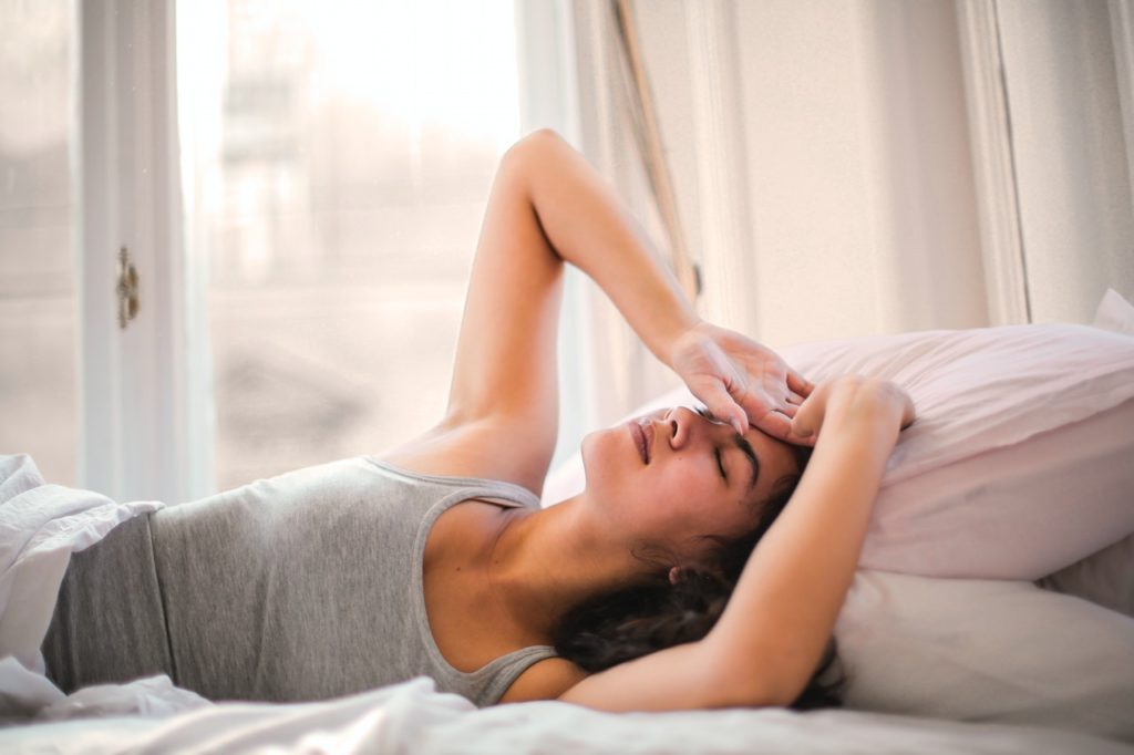 A woman with her hand on her forehead looking sick in bed.